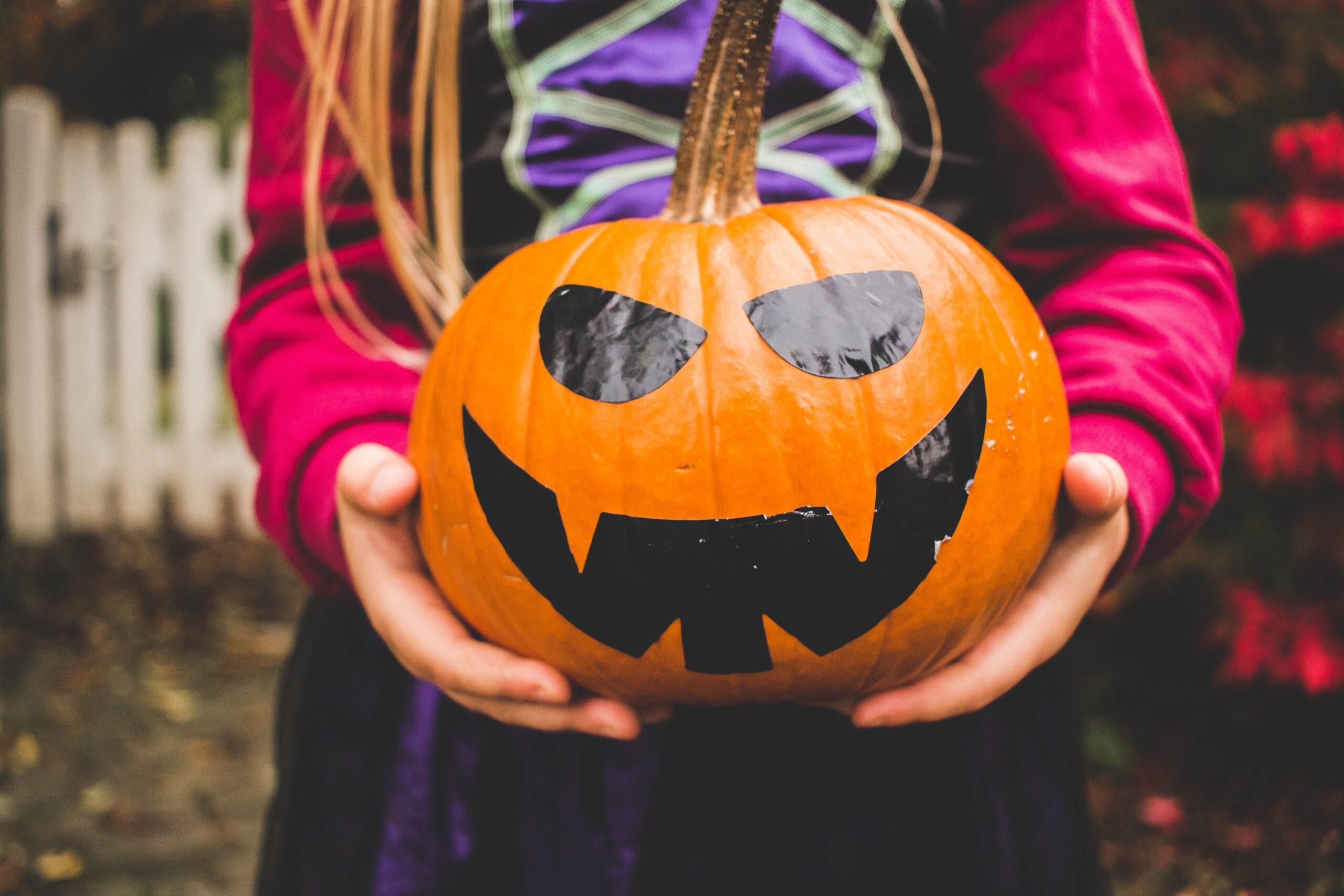 Kind hält dekorierten Halloween Kürbis vor Körper
